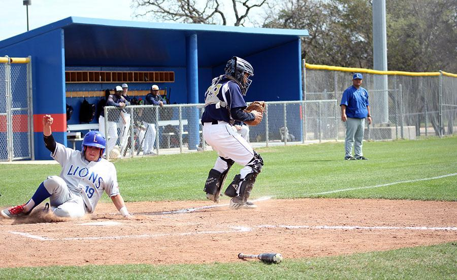 Senior Clay Martin slides into home to score against St. Dominic's. They went on to win 13-3.