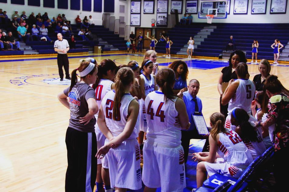 Coach Lamb huddles the team together during a timeout.