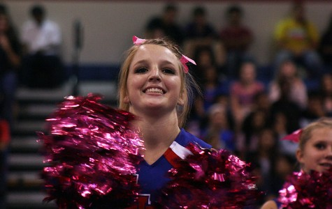 Junior Claire Jenkins cheering on the football team as they enter the pep rally last Friday.