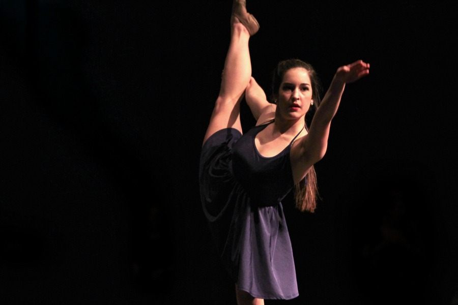 Senior Maria Young reaches out toward the audience in the Blue Belles dance to This Little Light of Mine.