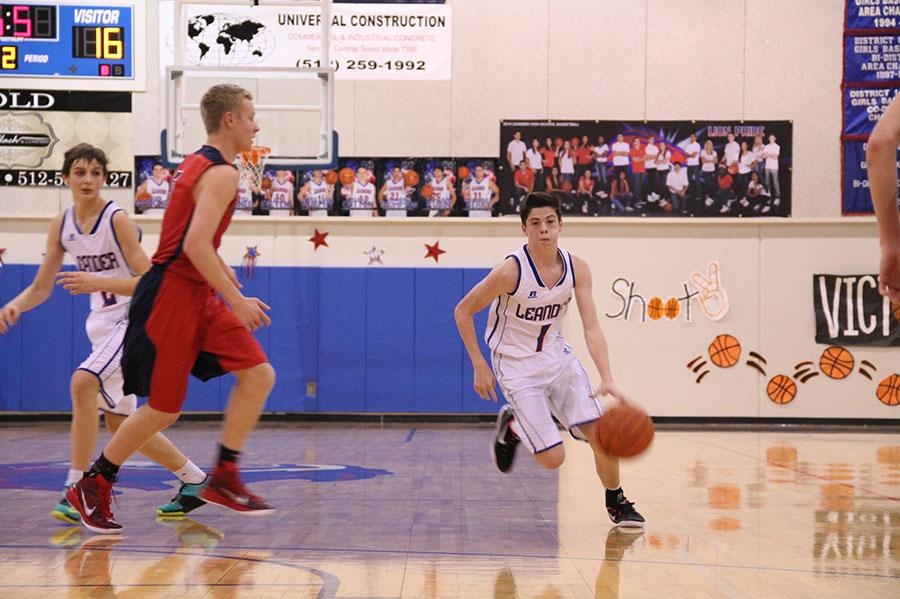 Sophomore Cody Bayer dribbles across the court towards the basket.