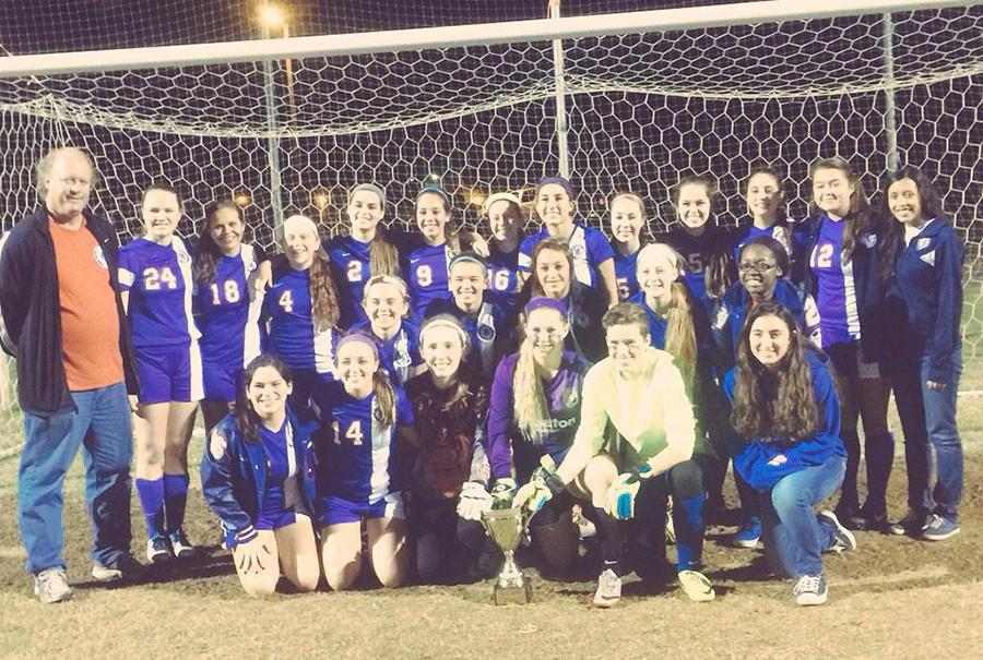 Varsity Girls' Soccer poses with their first place trophy from the Pleasanton Tournament.