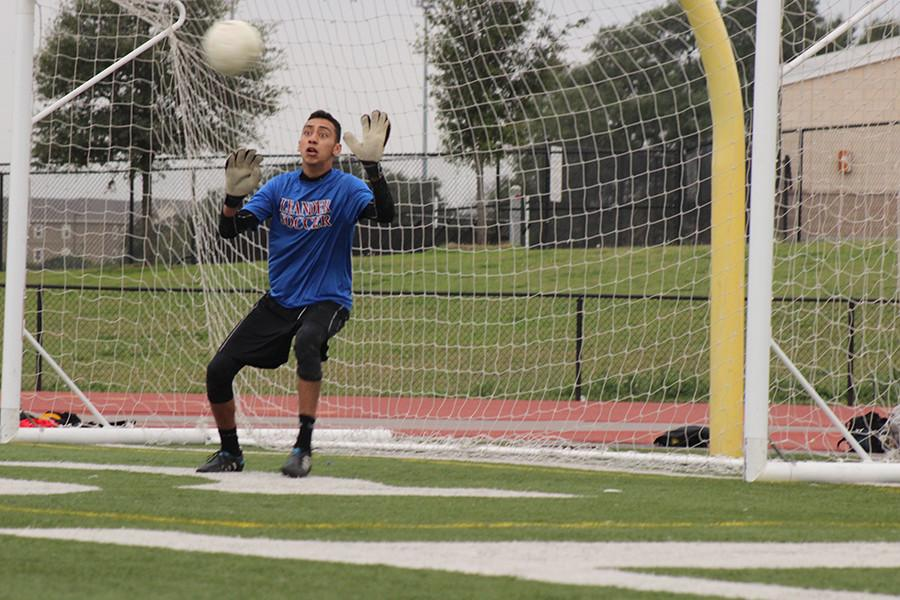 Senior varsity player Carlos Lopez moves to block a goal during team practice.