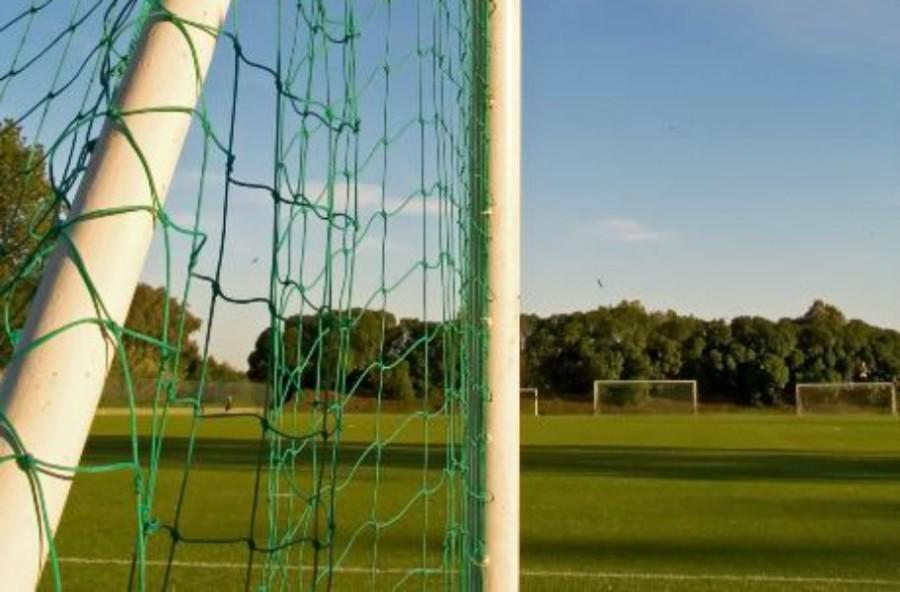 A goal post overlooking a soccer field.