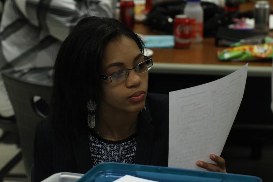 Senior Shekhiynah Larks studies notes before competiting in Lincoln-Douglas (LD) debate.
