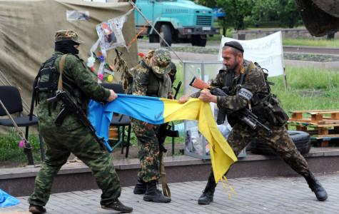 Pro-Russian fighters rip apart a Ukrainian flag outside a regional state building in Donestsk, Ukraine, on May 29, 2014