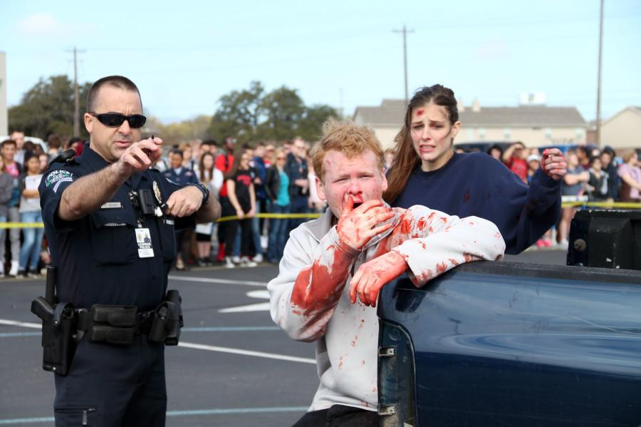 Corporal Bruce Trzeciak, senior Zane Hudson, and junior Sierra Stevenson watch as their loved ones are taken away by EMS