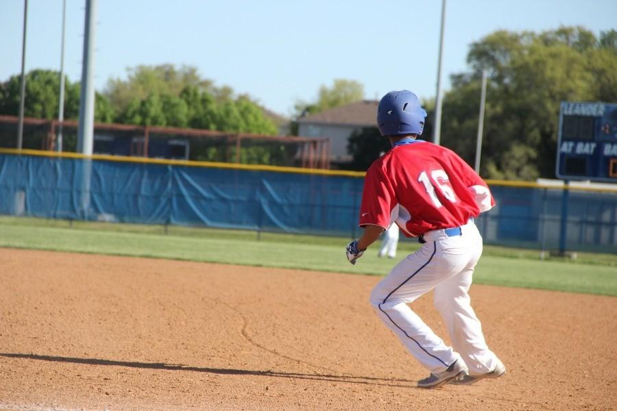 JV red player about to steal 2nd base