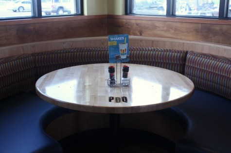 Rounded booth showing the brand of PDQ which lies on all of their dine-in tables