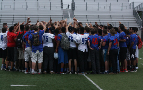The entire football team in a huddle after the spring festival. The festival included a band, cheer, and Blue Belle performance.