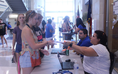 Students receiving information about textbooks. Certain classes are required to have textbooks this year, while many do not.