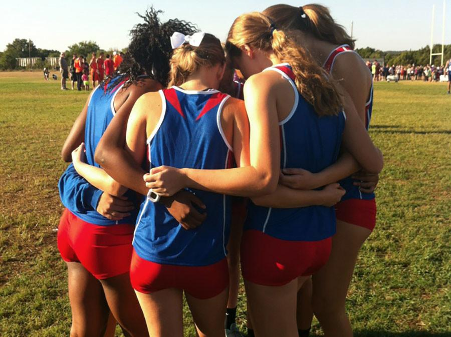 Varsity+girl+members+huddle+at+the+Liberty+Hill+meet+in+preparation+for+what+will+be+another+win+in+their+streak.