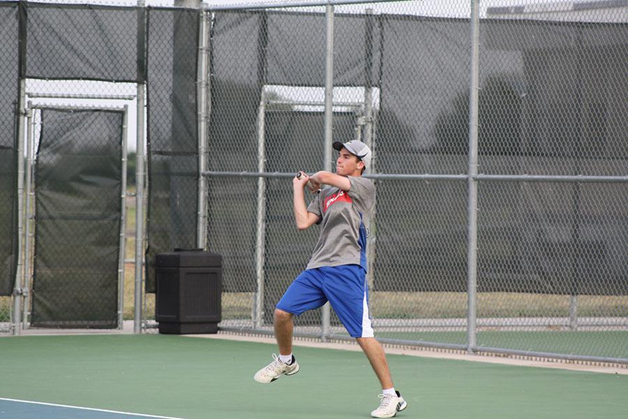 A Lions tennis player getting ready to swing during the tennis match against McNeil. The tennis team would later lose the game.