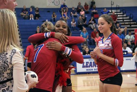 Sophomore Busi Banda sharing a moment with senior Callie Reed. The underclassmen stand on the sidelines while the seniors are being announced and celebrated.