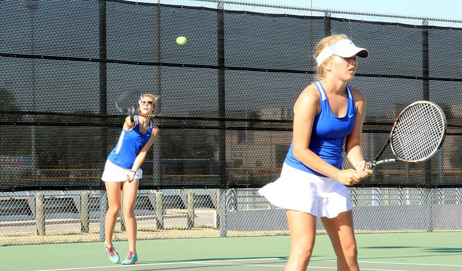 Tennis players serving the ball to the other team.  Varsity ended up losing both games against Cedar Park and East View.