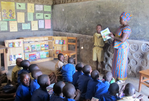 In Rwanda, Africa a 4th grade teacher reads a book to her class. Rwanda has a poor literacy rate teachers are trying to fix because the language spoken, Kinyarwanda, is only spoken in the small country of Rwanda so there are few books in the language.