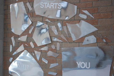 """A part of the IB art mural that says """"It Starts with You"""". This part of the mural is reflective."""