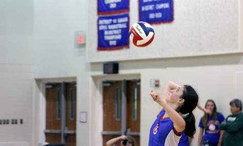 Junior Alyse Balderrama serving the ball during a match. This is a vital moment because the server could miss and a point would go to the opponent.