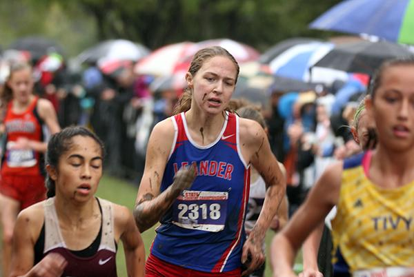 Claire Crone racing to the finish line. She was covered in mud because she had fallen twice during the race, coming out to place 52nd.