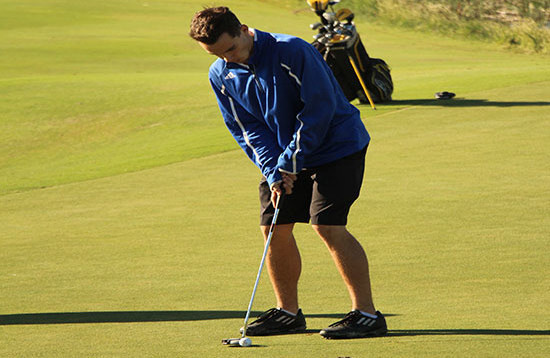 A boys golf member putting a golf ball. They would place fifth at Cottonwood Creek