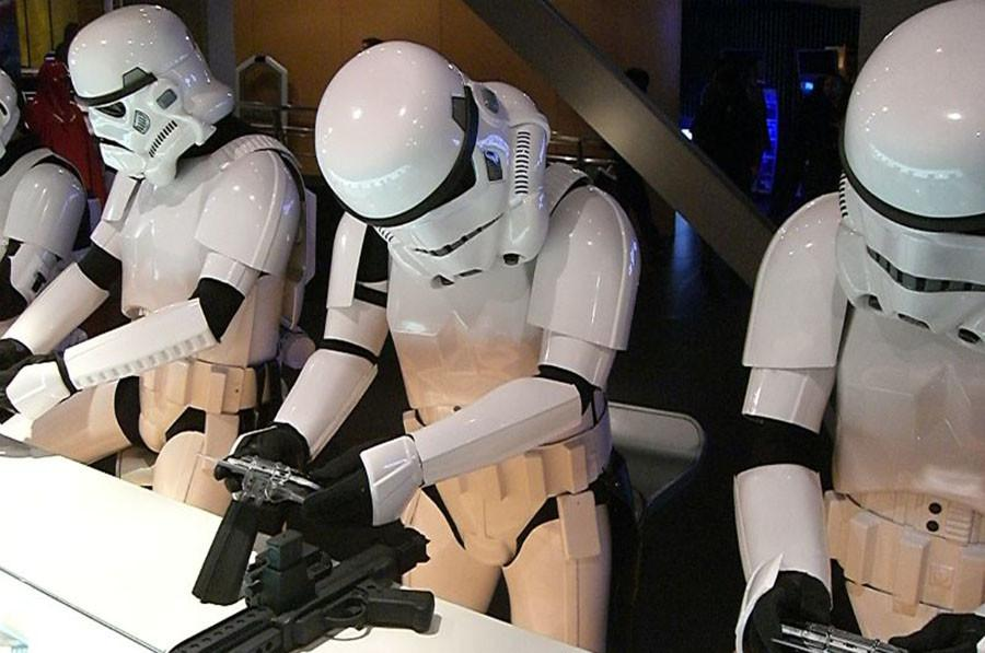 A bunch of stormtrooper playing video games. In the game players can play as rebels or imperials.