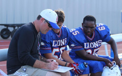 Freshmen Coach Kyle Sturgell reviews plays with members of the Blue team. The single victory on the Blue team's side came from the joint game.