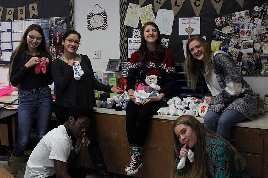 HOSA officers posing with their collected socks. The club collected over 100 pairs of socks.