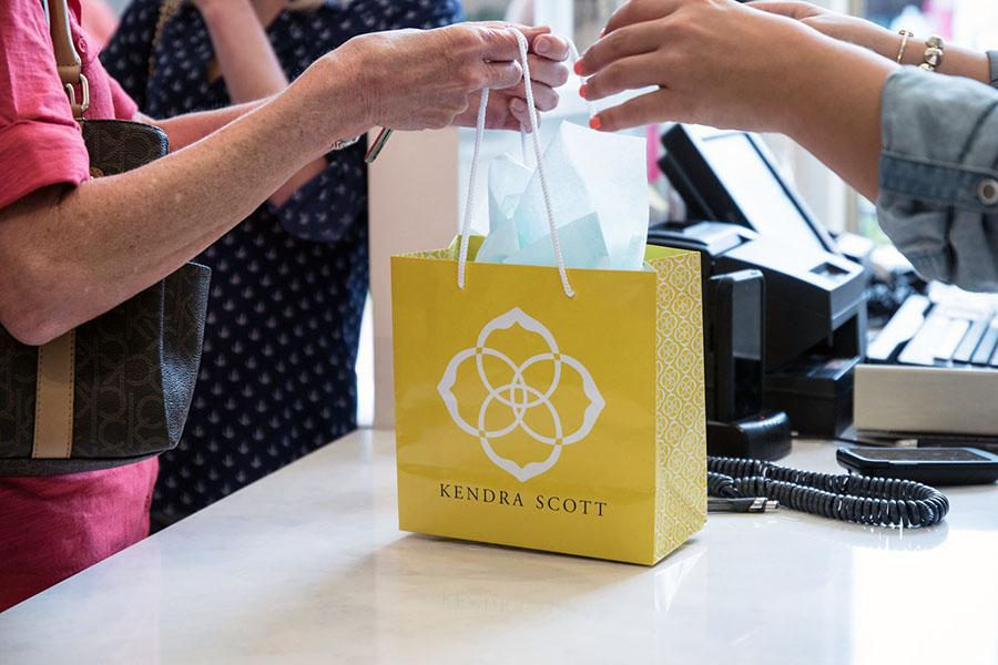 Kendra Scott bag displaying their logo.  At all times, 20% of their proceeds from their charms go to a local or national beneficiary.