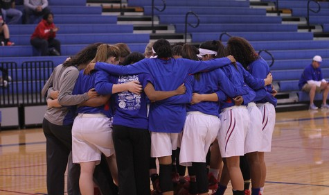 The varsity girls huddle together before a game. Some of the girls have played together since middle school.