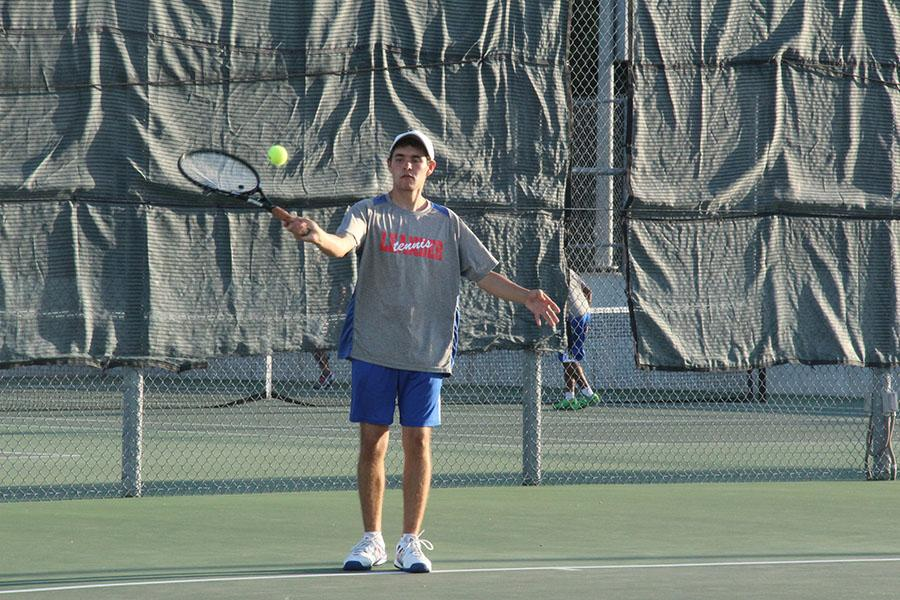 One of the doubles partners senior Luis Farias, hitting a ball towards an opponent. They won the consolation boys doubles 9-7.