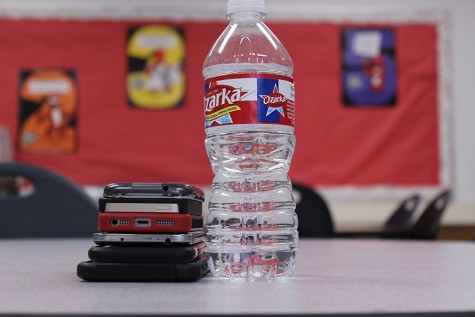 A stack of cellphones next to one water bottle, visually showing that people will be more smartphones than running water. In the year 2020 it is estimated that people will have more phones than water.