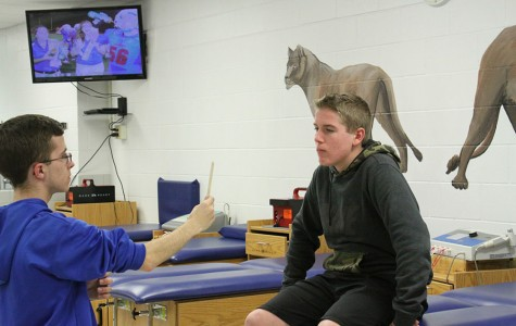 Freshmen Riley Wells and senior Zach Patton demonstrate how to test a concussion. Concussions can cause numerous types of injuries in numerous types of ways.