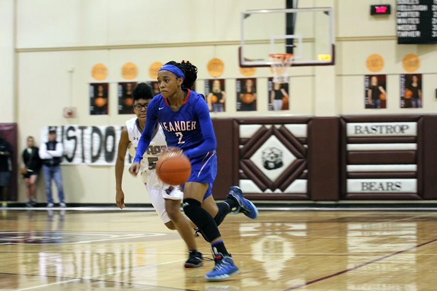 Senior Rayanna Carter runs across the court with the ball. She scored 26 points against Bastrop.