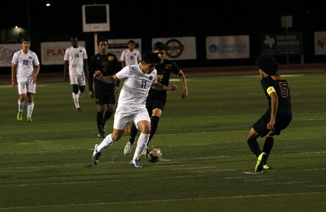 Senior Pedro Silva dribbles towards a defender. The boys tied this game 2-2.