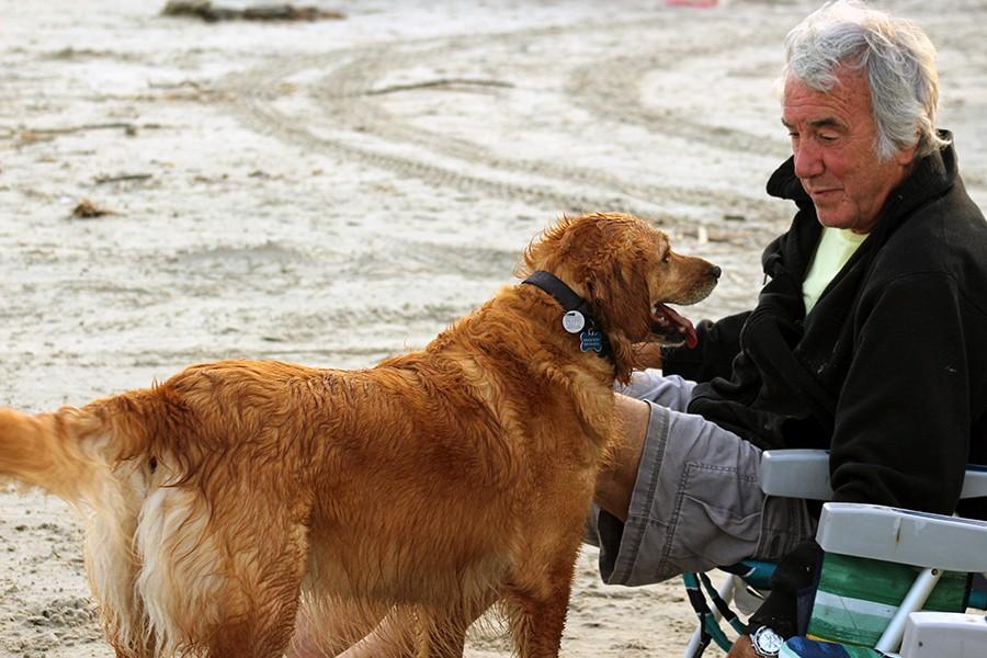 A man on the beach with his golden retriever Gracie. He owns two golden retrievers and loves them both dearly, the pictured one being 5 and the other 15.