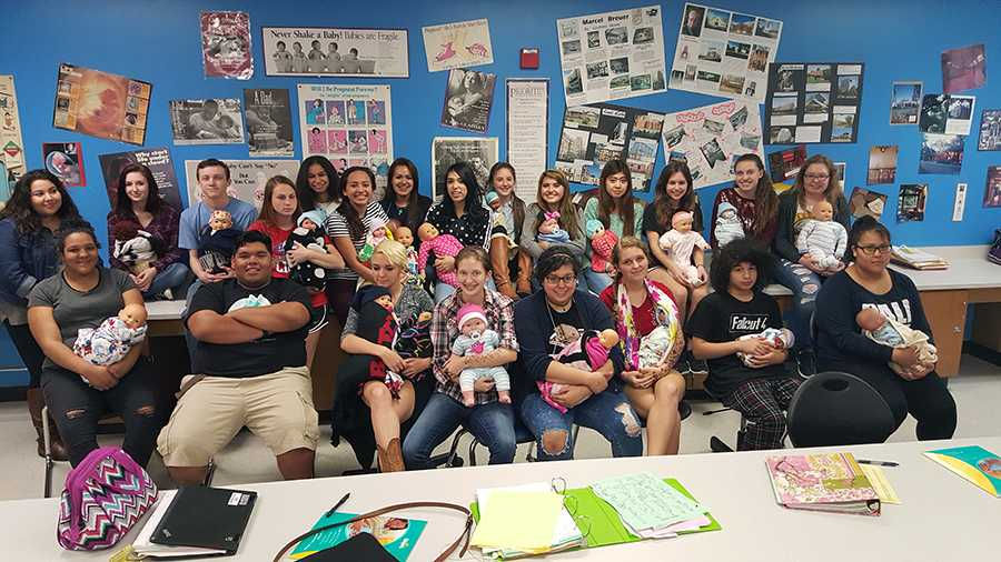 Ms. Rattan's class carries soda bottles dressed as babies for their project.