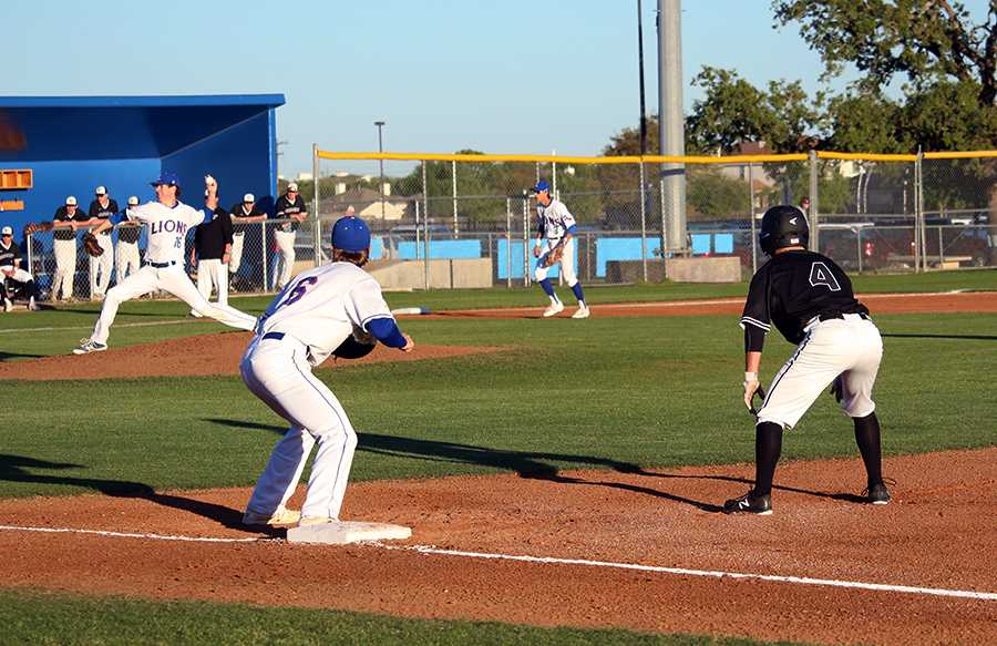 Senior Joel Miller pitching against the Vandegrift Vipers, and senior Trey Roberts covering 1st to stop opposing runner of stealing.