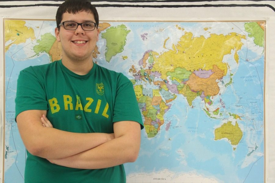 Senior Rafael Schoellmann behind a world map. He wishes to visit Nepal later in his life.