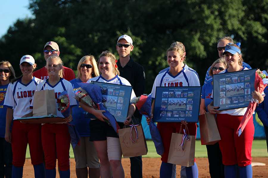 Seniors+Gabby+Walton%2C+Kellie+Jeanes%2C+Hailey+MacKay+and+Ashley+Burgess+after+receiving+their+gifts+for+senior+night.+The+gifts+include+a+collage+of+softball+photos+in+frames.