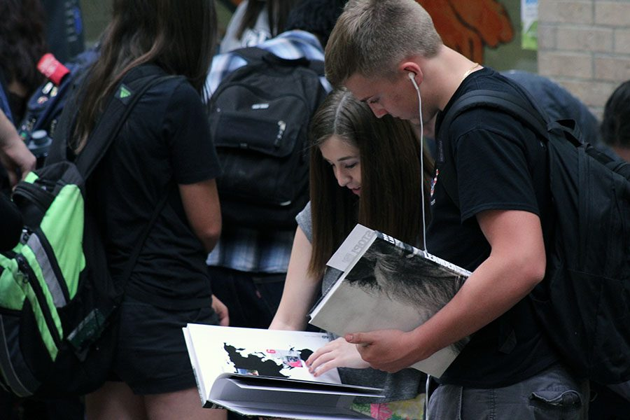 Two students looking at their yearbooks together after receiving them. Yearbooks are a big part of the end of the year for the students.