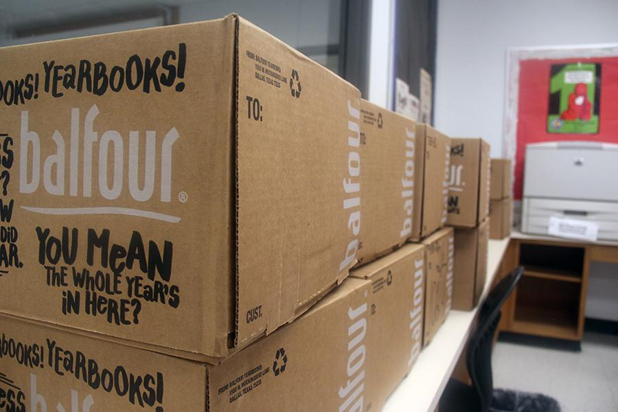 The boxes filled with yearbook in Mrs.Bell's room. The total weight of these boxes is 3,200 lbs.