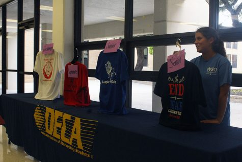 Senior Emilie Scanlon advertising shirt sales at the DECA table during lunch. All shirts are being sold for $15.
