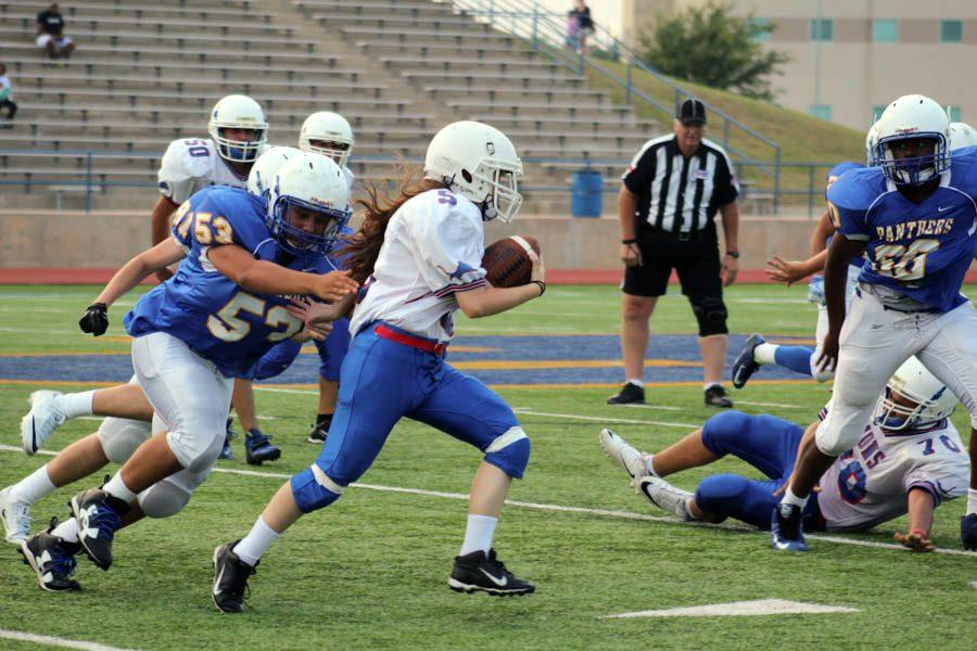 Freshman Staci Laramore runs the ball during the game against the Pflugerville Panthers. She is the only girl on the team of any level of football this year.