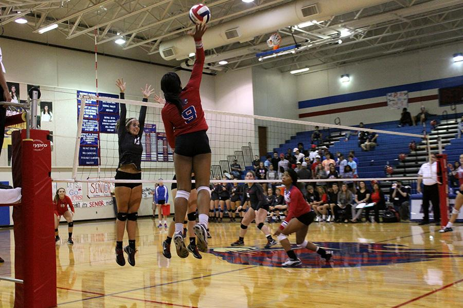 Junior Busi Banda and sophomore Lesley Hall playing Lake Travis. Busi is outside hitter, and Hall is middle blocker.