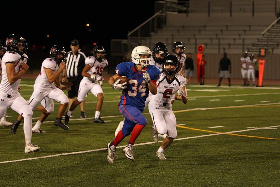 Sophomore running back Adison Larue breaks past the Lake Travis defensive line. Larue had his first scoreless game of the season against the Cavaliers.