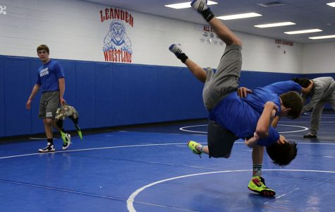 Sophomore John Geiger practices with another wrestler during the wrestling period. The Lions wrestled to third place in their first tournament.