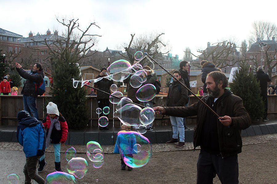 Outside the Rijksmusuem at a Christmas market a man makes giant bubbles for money. All around the market were musicians and other street performers.