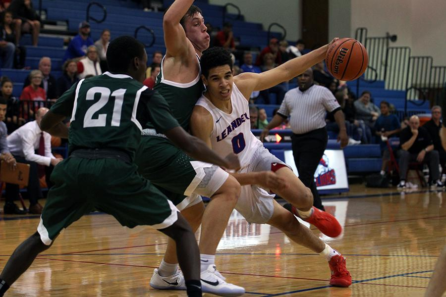 In a previous game, senior Kobe Thompson falls into an opposing player. Thompson plays guard, point guard, and forward for the Lions.