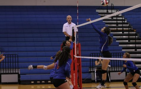 The varsity girls jump  to make a block against Westlake. They have two games left until District.