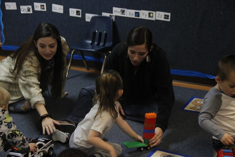 Juniors Madison Stathos and Abbey Saunders spending time with kids who attend Head Start. This is their first year in the program.